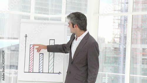 portrait of a businessman showing statistics during presentation
