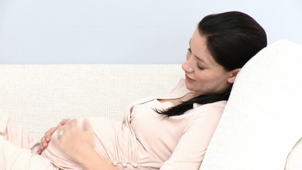 pregnant woman lying on her sofa at home