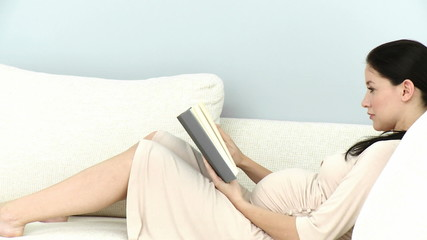 pregnant woman reading lying in the living-room