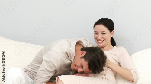 Loving couple expecting a baby sitting on sofa