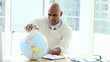 Ethnic businessman looking at a terrestrial globe