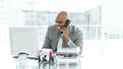 Joyful businessman talking on phone