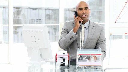 smiling african businessman on phone sitting in his office