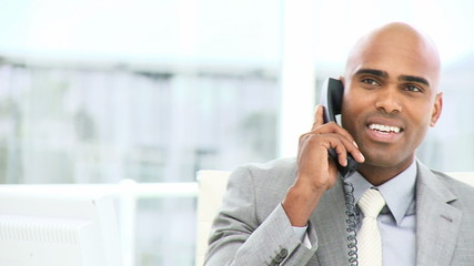 confident business man on phone sitting in his office