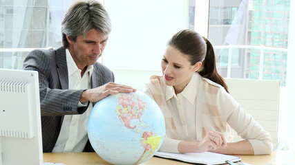 Serious business co-workers looking at a terrestrial globe