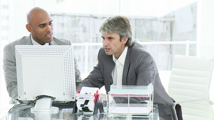 two men working at a computer having an argument