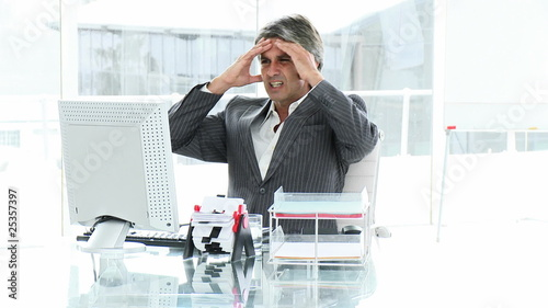 angry man working with his computer sitting in his office