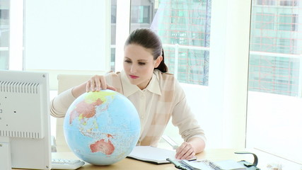 attractive young executive looking at a terrestrial globe