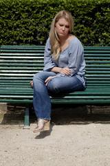 jeune femme triste assise sur un banc