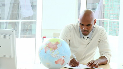 african business man writing looking at a terrestrial globe
