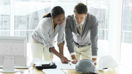 two attractive architects studying blueprints