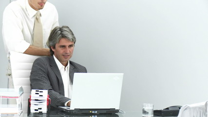 businessmen looking at a laptop in their office with secretary