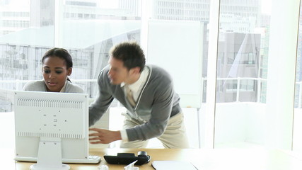 businesswoman at a computer having an argument with colleague