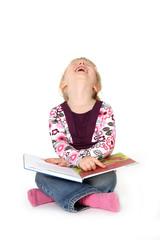 Kind lacht beim Buch anschauen