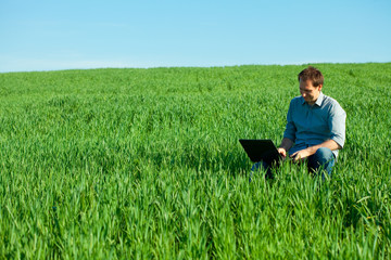 young man using laptop in the field