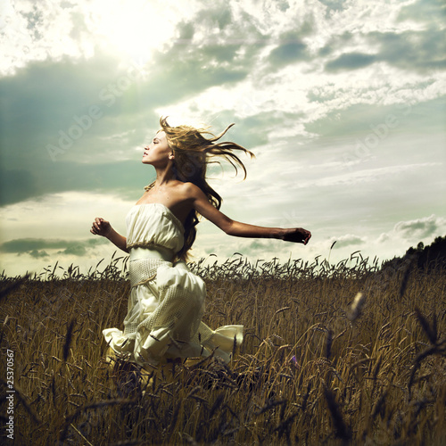 Wall mural Girl running across field