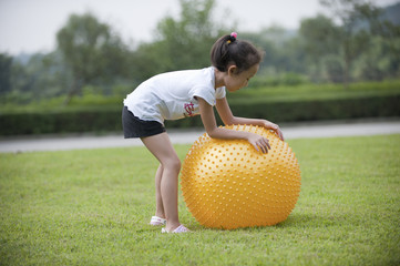 asian girl play ball on grass