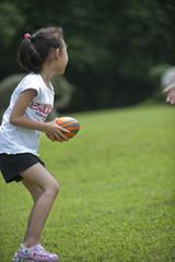 asian girl play ball on grass