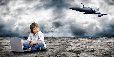 Young boy seating with notebook on the land and military plane