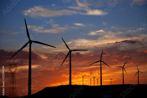 Wind turbines against a fiery sunset