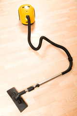Vacuum cleaner on the polished wooden floor