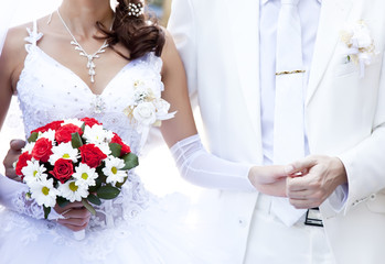 Bridegroom and bride holding beautiful red roses wedding flowers