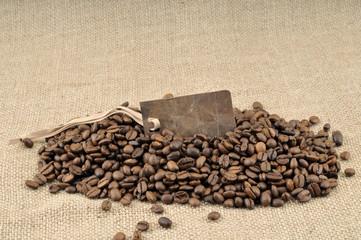 Vintage tag on coffee beans and jute background