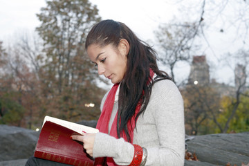 Girl reading Bible in park