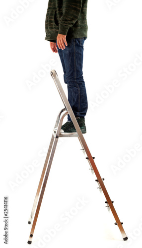 young man in dark clothes standing on metal ladder
