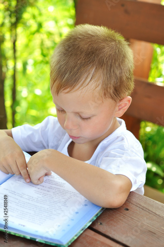 little boy reads book outdoors