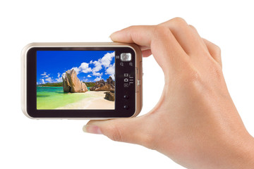 Hand with camera and beach landscape (my photo)