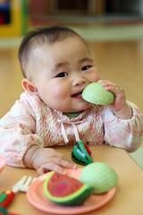 メロンのおもちゃをかじる赤ちゃん