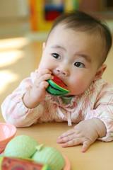 スイカのおもちゃをかじる赤ちゃん