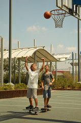 Two boys playing basketball standing on a skateboard .