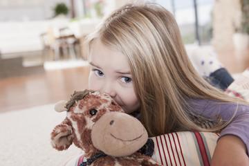 Deutschland, Mädchen mit Stofftier, liegen auf Teppich