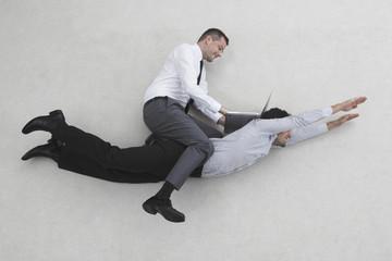 Zwei Geschäftsleute, einer von ihnen fliegt, der andere sitzt auf seinem Rücken