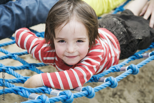 germany, berlin, boy (3-4) lying on jungle gym, portrait