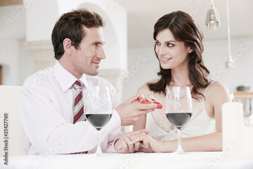 couple sitting at table in restaurant, man holding gift parcel