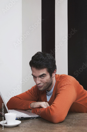 man raised eyebrows with laptop and coffee cup