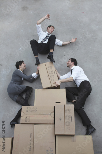 three business people balancing on cardboard boxes, smiling, portrait, elevated view