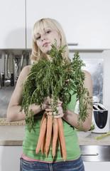 Deutschland, Frau jung in der Küche mit Bund Karotten, Portrait