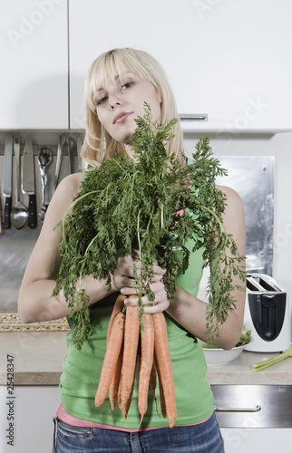 germany, berlin, young woman in kitchen holding bunch of carrots, portrait