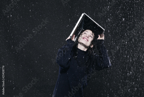 woman sheltering from rain under laptop.