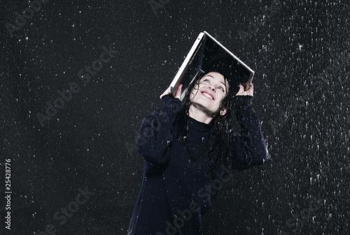 Junge Frau schütz sich mit einem Laptop vor dem Regen