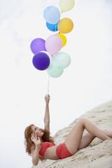 Deutschland, Bayern, Junge Frau auf Sanddüne mit Luftballons