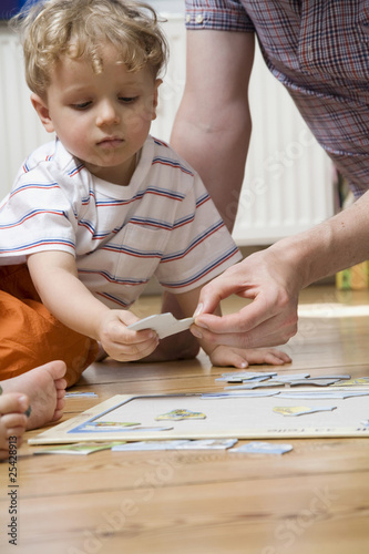 germany, berlin, father helping son (3-4) to put puzzle together