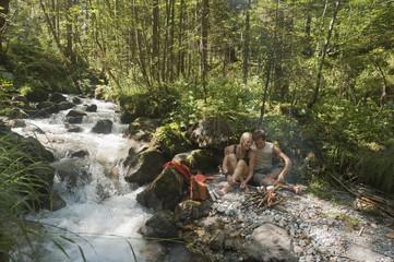 Österreich, Steiermark, Junges Paar sitzt am Lagerfeuer, Bach, Wald