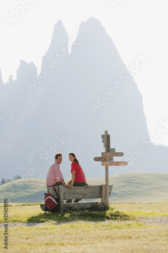 italy, south tyrol, seiseralm, couple sitting on bench