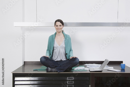 woman relaxing on desk with laptop