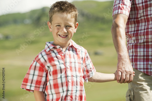 italy, seiseralm, grandfather and grandson (6-7) hand in hand, smiling, portrait, close-up